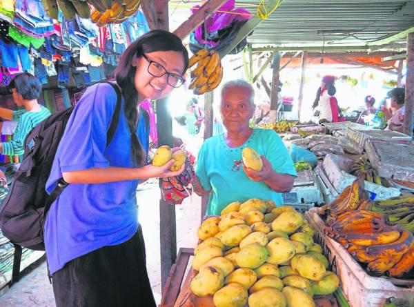 巧遇多巴湖市集,用布袋买了几粒芒果,硬要和老奶奶合照。