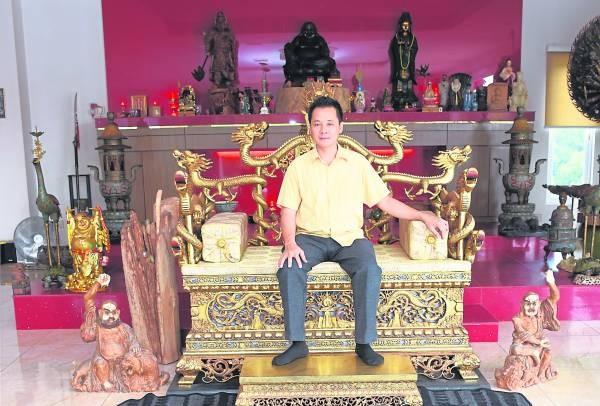 """刘慧官博士坐在超过百年历史的皇帝龙椅上,大有""""君临天下,唯我独尊""""的不凡气派。而他身边的每一件古董,个个都大有来历,价值连城。"""
