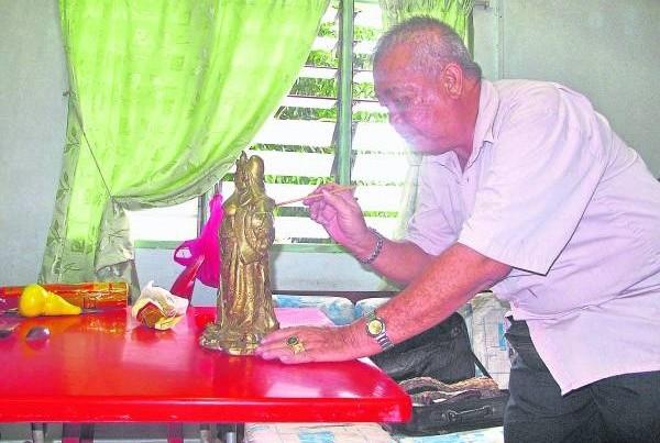 吴俊融师父重新为旧神像上金漆。