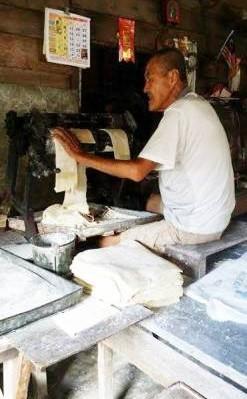 廖炳鸿老练的手法操作着手摇式的搅面机。