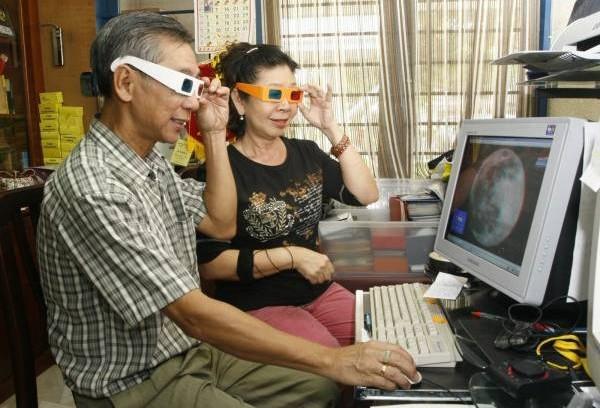 张升荣和何桂花尝兴趣相投,试以3D眼镜观看月球表面。