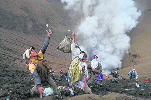 数百名印尼人,拿着网兜来到火山口边,准备接住当地腾格尔部族为祭祀山神而扔进火山口的供品,以期求得好运。