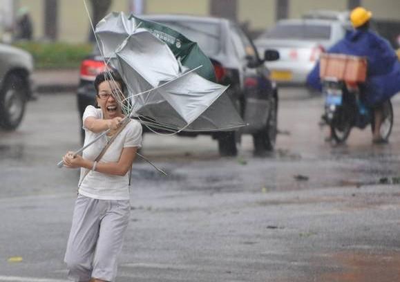 """台风""""海燕""""袭击琼海市街头,一名行人的雨伞瞬间遭强风折断。"""