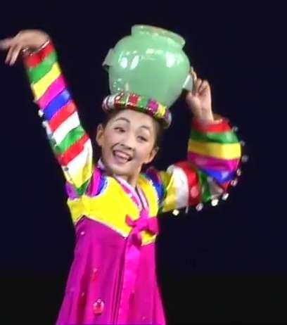 小女孩头上顶着一个比头还大的水罐,动作优雅,接着不断转圈圈。