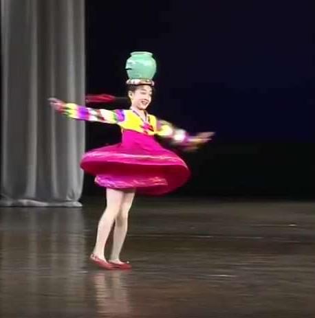 她越转越快,越转越快,转到台下观众看了头晕,水罐仍然稳稳顶在头上。