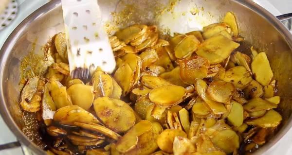 倒入黑糖和三温糖,将糖和姜片拌炒均匀。姜片会释出水分,糖则会溶解,所以你会看到锅内有黑色的姜汁。