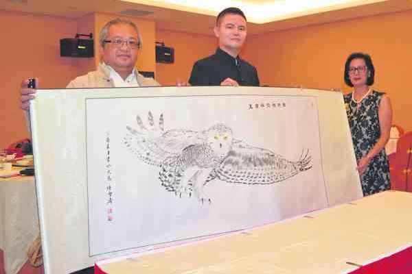 陈雪涛老师(左)的得意之作之一《雪鸮横空称霸王》,展翅高飞的雪鸮气势磅礴!中间为拿督吴承澔博士,右为陈雪涛老师爱妻胡美华。