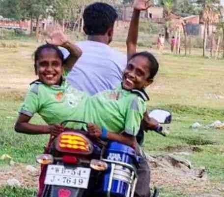 连体姐妹坐在电单车上,心情很好。