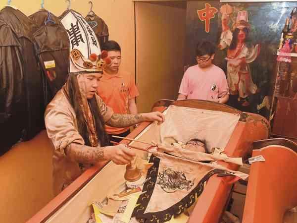大爷伯指定的梅花棺体积比一般棺木来得硕大,质感更为厚实沉重,其上悬挂一把印有太极八卦图的法伞,据说有聚集能量的用途。