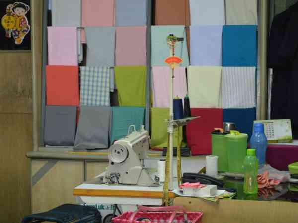 韩勇贺的工作空间不大,但缝纫机、各色布匹、工具等排列得非常整齐。