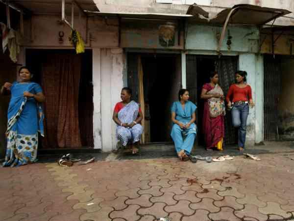 走入妓女村,随处可见在屋前等待客人的妓女。