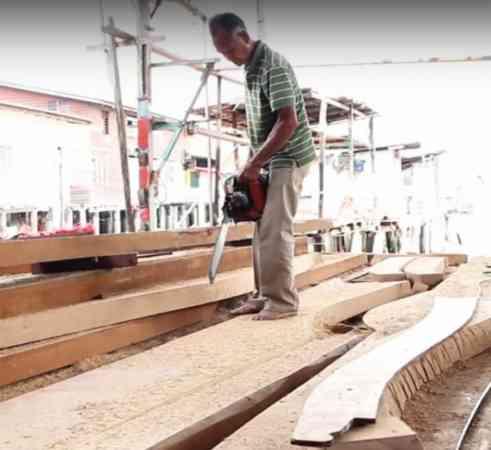 老当益壮的吴文光拿起电锯,熟练的技术,快速将木板锯开。