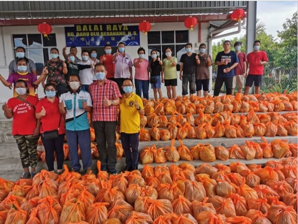 工作人员将已包装好的新鲜蔬菜排放整齐,准备送往居民家。(照片取自《中国报》)