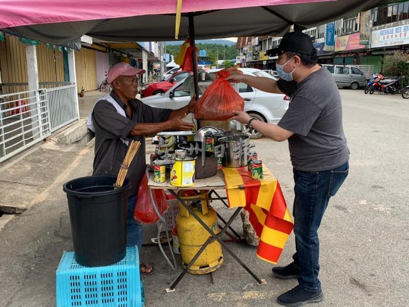 陆兆福(右)亲自移交食物援助品给在路边摆摊的小贩。(照片取自《星洲日报》)