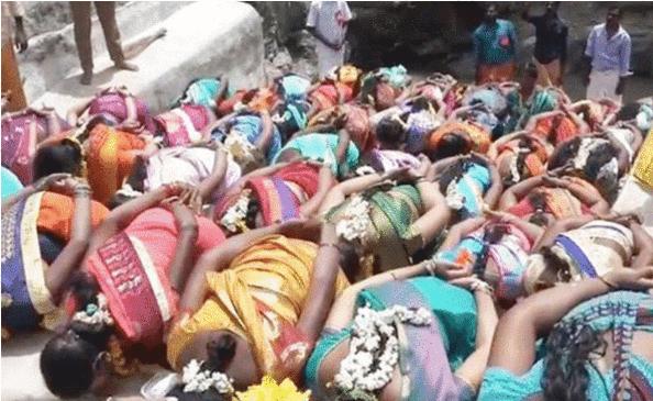 十几名想怀孕的妇女排成一列趴在地上,等待苦行僧从她们背上踩过。