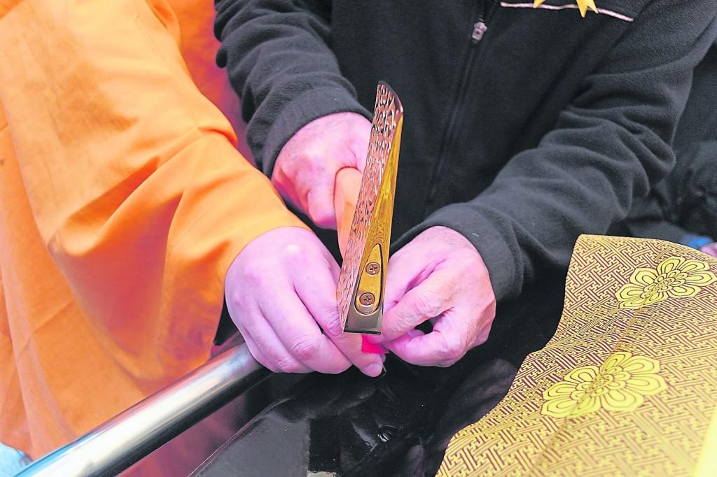 """通常""""安钉""""时是在点钉盘上置一把系红布的斧头,一根系红布的铁钉,一块红布给点钉者披肩示吉。"""