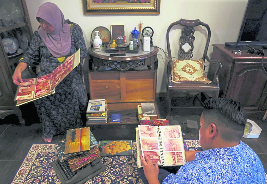 """现年40岁的新加坡""""东姑""""阿赞与妈妈一起看旧时候的家庭照。"""