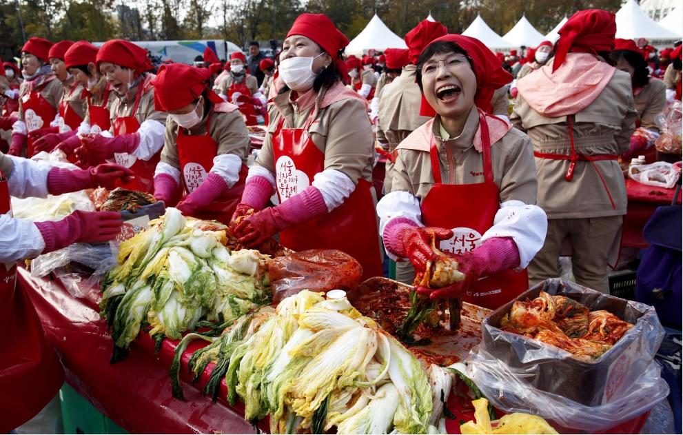 """2014年11月14日,韩国养乐多公司举办""""做泡菜送邻里""""的活动,召集了上千名养乐多阿珠妈在首尔市政厅前做泡菜。"""