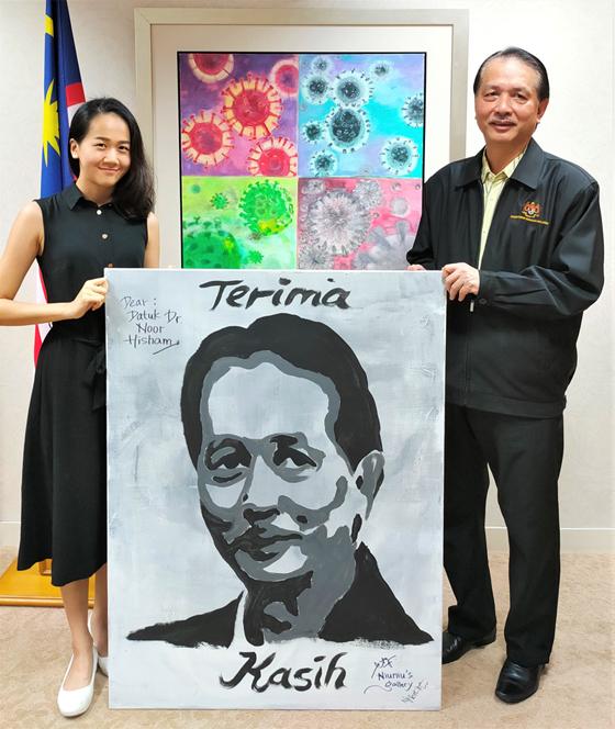 在疫情期间把致敬的画作亲自送到抗疫英雄卫生总监丹斯里诺希山的手上。