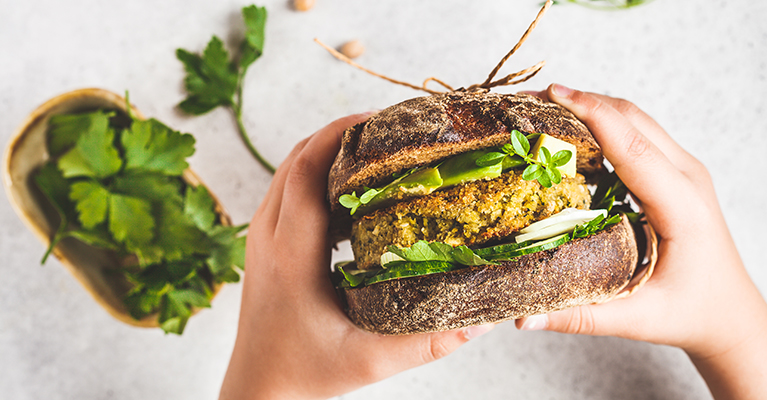 Vegan sandwich with chickpea patty, avocado, cucumber and greens