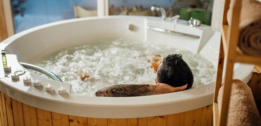 Man relaxing at home in the hot tub bath ritual with a glass of wine.Spa day moment in bathroom indoors jacuzzi tub.Leisure activity.Good personal hygiene routine.Skincare,aromatherapy.Antistress