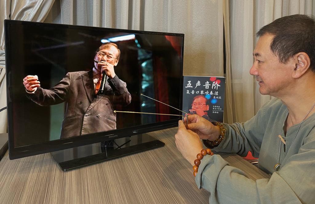 陈博士透过屏幕为大马世界级口琴大师,马来西亚华人文化协会总会长张雅诰进行能量棒远程测试。