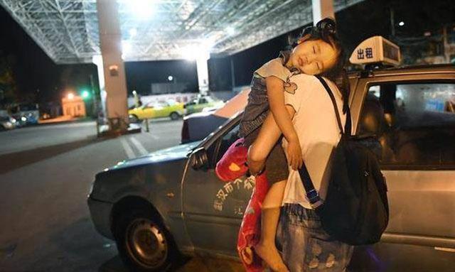 李少云抱着熟睡的女儿,行走在夜色中。